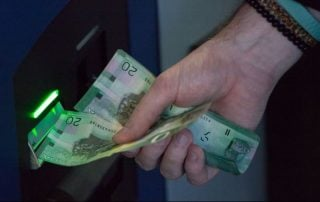 Man receiving stack of $20 from ATM