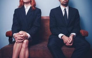 Suited woman and man sat on bench with arms crossed