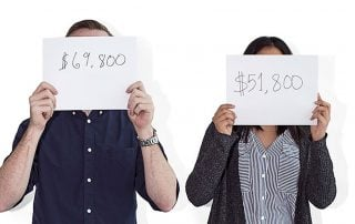 Man holding a sign which reads $69,800/yr and woman holding a sign reading $51,800/year