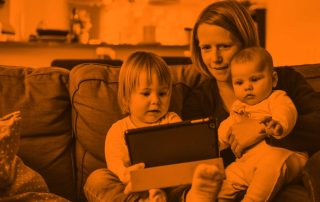 Mother holding her two children on a couch, while eldest hold a tablet