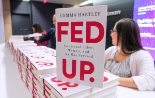 "Cover of book ""Fed Up"" stacked on event registration table"