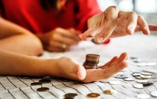 Counting and stacking coins on the palm of a hand