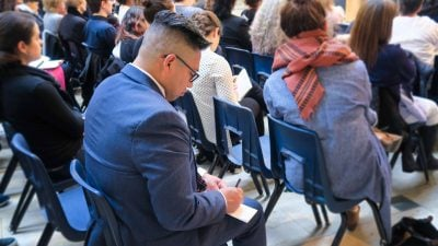 Audience member writing notes