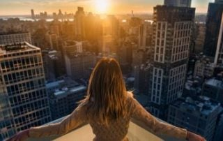 A woman holding out her arms facing the cityscape
