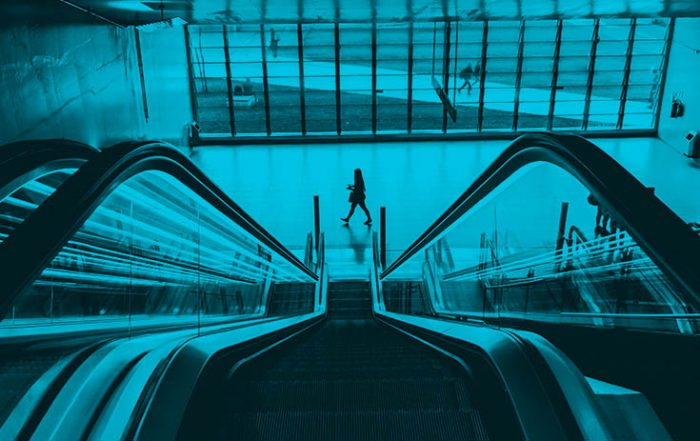 View from top of the escalator with a woman walking by at the bottom