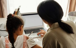 Mother and daughter homeschooling in front of laptop