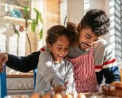 Father cooking with daughter at kitchen table