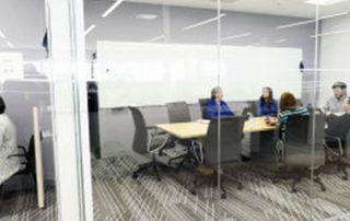 Exterior shot of boardroom with four members sitting inside