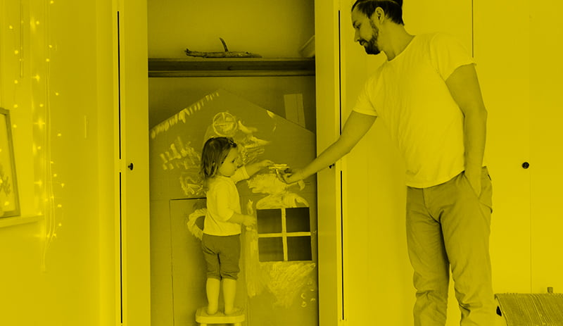 Father handing paintbrush to daughter painting play house