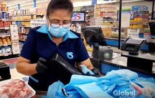 Female grocery cashier scanning items at chekcout