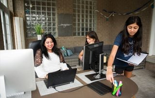 Woman working at her home office while her two daughters assist