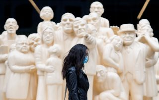 Woman with mask walking past series of statues
