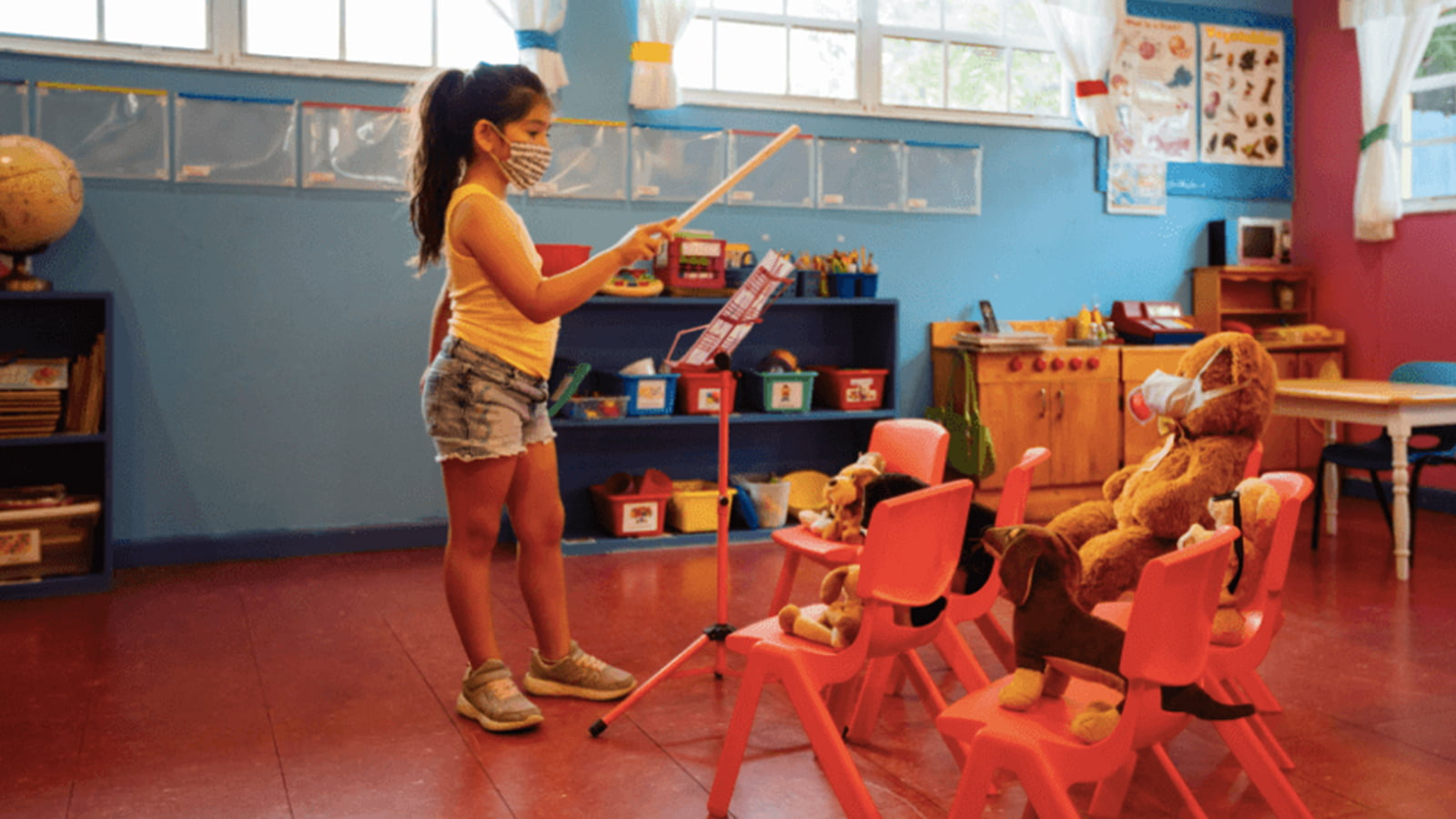 Young girl in face mask conducting music in an empty classroom