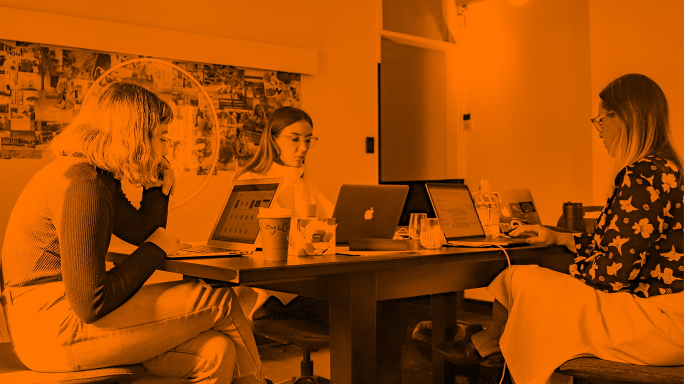 Office with three women sat at desk with their laptops