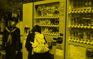 Two school girls looking at vending machine