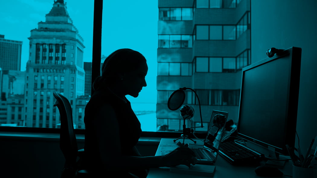 Silhouette of woman sat at computer desk in business office