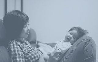 Mother sat on couch holding baby in her lap