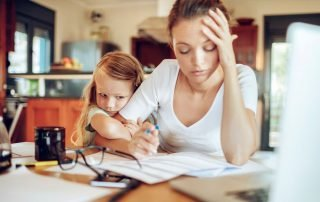 Woman sat at desk working with child hold on to her arm